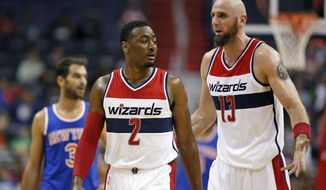 FILE - In this Oct. 9, 2015 file photo, Washington Wizards guard John Wall (2) and Washington Wizards center Marcin Gortat (13), from Poland, talk in the first half of an NBA preseason basketball game against the New York Knicks, in Washington. With their backcourt of All-Star John Wall and Bradley Beal leading the way, the Washington Wizards hope they can overcome the departure of Paul Pierce to return to the playoffs. (AP Photo/Alex Brandon, File)