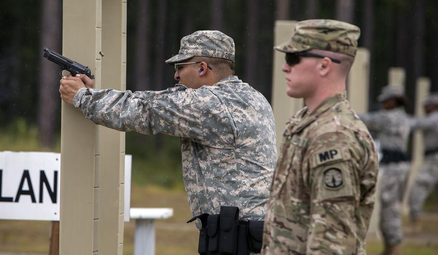 A 9mm case is ejected from the chamber of a Beretta M9 during a qualifying exercise for the 139th Military Police Company, Tuesday, Sept. 29, 2015, in Fort Stewart, Ga.  The Army wants to replace its M9, a 9mm semi-automatic handgun adopted during the Cold War. The new gun also will replace the smaller M11.  (AP Photo/Stephen B. Morton)