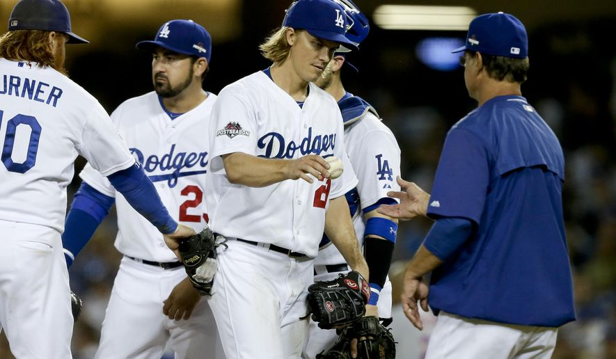 Los Angeles Dodgers starting pitcher Zack Greinke hands the ball to manager Don Mattingly, right, as he leaves the game during the seventh inning in Game 5 of baseball's National League Division Series against the New York Mets Thursday, Oct. 15, 2015, in Los Angeles. (AP Photo/Alex Gallardo)
