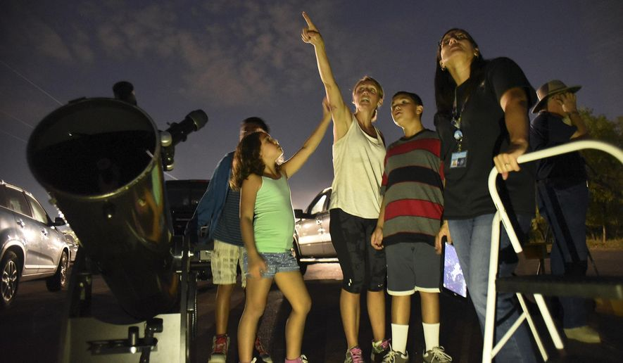 Shannon Durante points out a feature in the night sky to her children, Selah, left, and Isaac as Christine Coco, right, during a stargazing gathering with San Antonio Astronomical Association (SAAA).  at McAlister Park on Oct. 7, 2015 in San Antonio, Texas.  For years, SAAA has set up towering Dobsonians, compact Schmidt-Cassegrains and other powerful telescopes in a McAllister parking lot near some too-well-lit soccer fields. And despite growing light pollution, the group continues to open many a squinted eye to the wonders of the cosmos.  (Billy Calzada/The San Antonio Express-News via AP) RUMBO DE SAN ANTONIO OUT; NO SALES; MANDATORY CREDIT