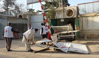 Afghan employees of a Doctors Without Borders hospital move debris of its damaged gate in Kunduz, Afghanistan, Thursday, Oct. 15, 2015. (AP Photo/Najim Rahim)