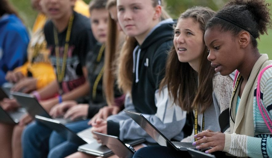 In this photo taken Thursday, Oct. 15, 2015, Wilson Middle School students access the free BLink Wi-Fi during a press conference at the Charles E. Lakin Human Services Campus in Council Bluffs, Iowa. (Joe Shearer/The Daily Nonpareil via AP) MANDATORY CREDIT