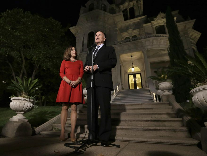 FILE - In this Nov. 4, 2014 file photo, Gov. Jerry Brown, accompanied by his wife, Anne Gust Brown, smiles as he talks to reporters outside the Old Governor's Mansion State Historic Park after winning re-election. The governor's office announced Friday, Oct. 16, 2015, that the Browns and their two dogs will move into the mansion after completion of a $1.6 million renovation, later this year.  The mansion, built in 1877, has not housed a chief executive since Ronald Reagan in 1967. (AP Photo/Rich Pedroncelli, file)