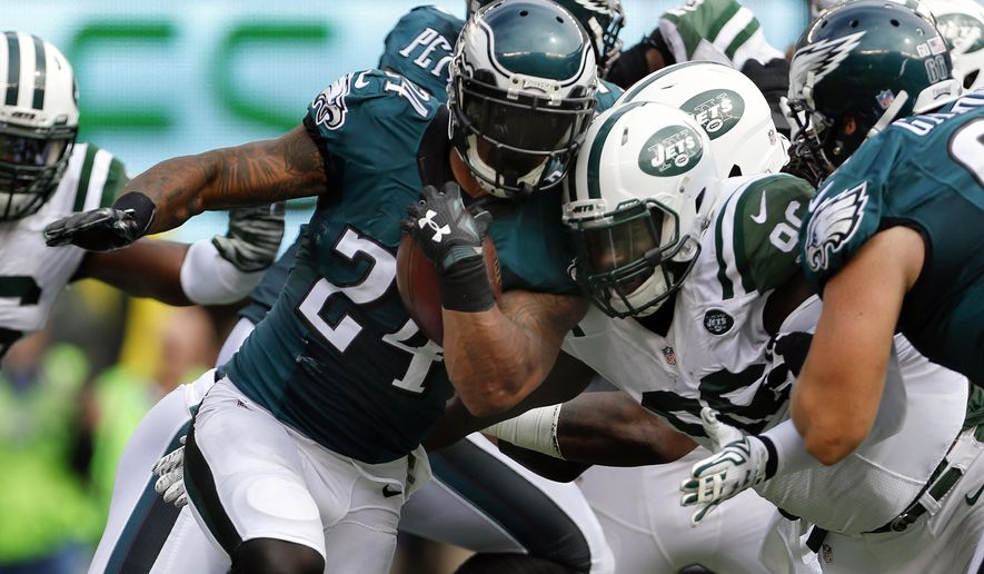 FILE - In this Sept. 27, 2015, file photo, Philadelphia Eagles running back Ryan Mathews (24) is hit by New York Jets defensive end Muhammad Wilkerson (96) as he runs the ball during the second quarter of an NFL football gam in East Rutherford, N.J. Opposing offenses have been stopped 18 straight times in third-down situations, the Jets' longest streak of stinginess since 2010, when they had 21 in a row. (AP Photo/Adam Hunger, File)