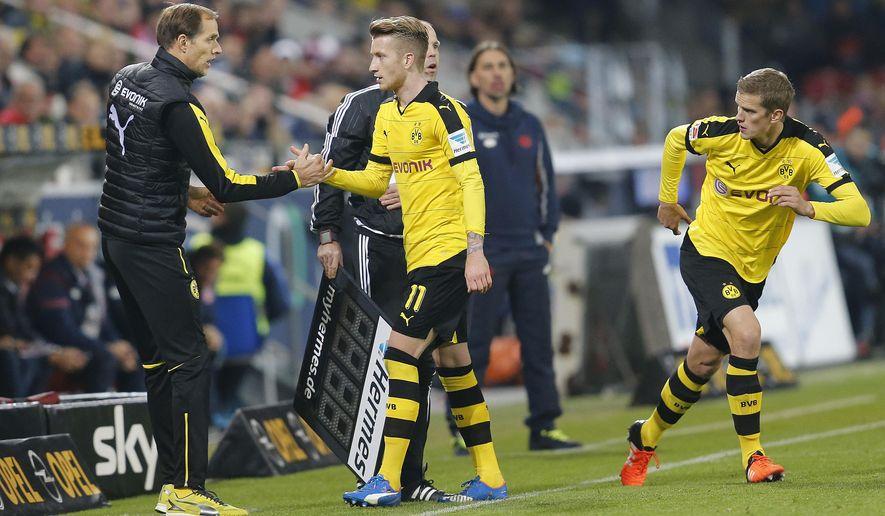 Dortmund head coach Thomas Tuchel, left, shakes hands with Dortmund's Marco Reus during a German Bundesliga soccer match between FSV Mainz 05 and Borussia Dortmund in Mainz, Germany, Friday, Oct. 16, 2015. (AP Photo/Michael Probst)