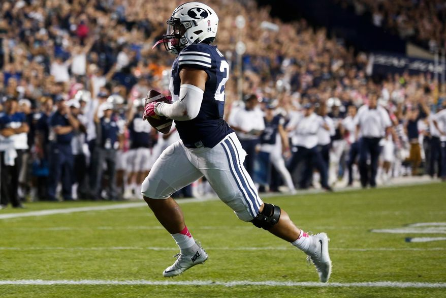 BYU running back Algernon Brown runs the ball in for his team's first touchdown against Cincinnati in the first half of an NCAA college football game Friday, Oct. 16, 2015, in Provo, Utah. (Spenser Heaps/The Daily Herald via AP) MANDATORY CREDIT