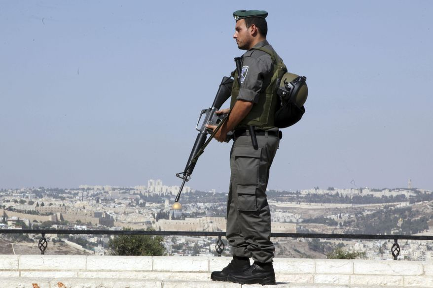 An Israeli border policeman stands on a hill overlooking Jerusalem's Old City, Saturday, Oct. 17, 2015. Palestinian assailants carried out a series of five stabbing attacks in Jerusalem and the West Bank on Saturday, as a month-long outburst of violence showed no signs of abating. (AP Photo/Mahmoud Illean)