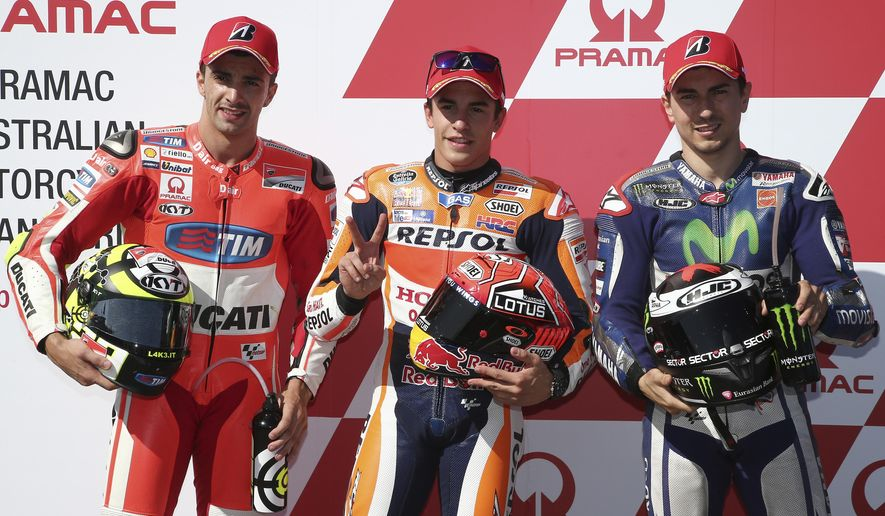 MotoGP rider Marc Marquez of Spain, center, holds up two fingers as he celebrates with Jorge Lorenzo of Spain, right, and Andrea Iannone of Italy after qualifying for the Australian Motorcycle Grand Prix at Phillip Island, Australia, Saturday, Oct. 17, 2015. Marquez took poll ahead of Iannone and Lorenzo. (AP Photo/Rob Griffith)