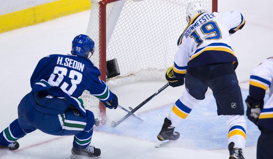 St. Louis Blues' Jay Bouwmeester, right, pulls the puck off the goal line to prevent Vancouver Canucks' Henrik Sedin, of Sweden, from scoring during the third period of an NHL hockey game, Friday, Oct. 16, 2015, in Vancouver, British Columbia  (Darryl Dyck/The Canadian Press via AP) MANDATORY CREDIT