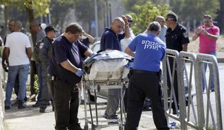 The body of an alleged Palestinian attacker is removed from the scene in Jerusalem Saturday, Oct. 17, 2015. Police spokeswoman Luba Samri said a 16-year-old Palestinian drew a knife on officers when they approached him in Jerusalem and asked for identification Saturday. She said the officers opened fire and killed him. (AP Photo/Mahmoud Illean)