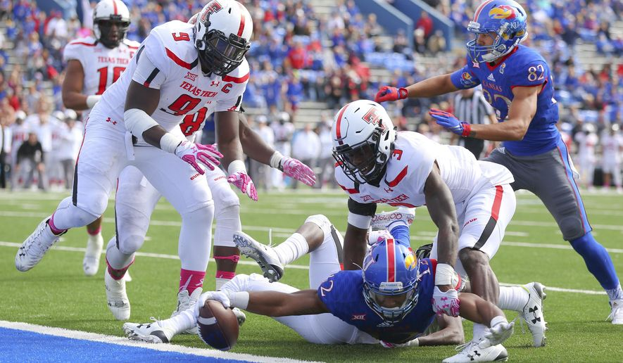 Kansas wide receiver Darious Crawley reaches the ball across the goal line for a touchdown as he is defended by Texas Tech defensive back J.J. Gaines (3) and defensive lineman Branden Jackson (9) during the second half of an NCAA college football game on Saturday, Oct. 17, 2015,  at Memorial Stadium in Lawrence, Kansas. (Nick Kruf/The Journal-World via AP)