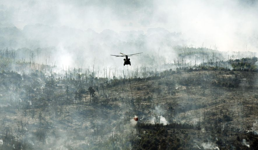 A helicopter drops water on the Hidden Pines Fire in Smithville, Texas, on Friday, Oct. 16, 2015. A preliminary investigation indicates a farming accident sparked a wildfire that's consumed more than 7 square miles and destroyed 40 structures in Central Texas, authorities said Friday. (Jay Janner/Austin American-Statesman via AP)
