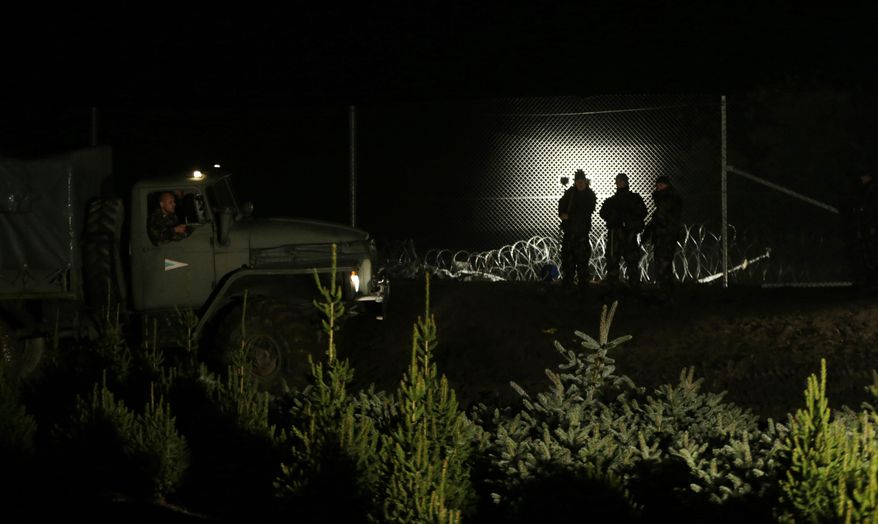 Hungarian soldiers stand by a fence put on the border with Croatia near the village of Zakany, Hungary, Saturday, Oct. 17, 2015. Hungary shut down its border with Croatia to the free flow of migrants on Saturday, a move experts say could leave thousands of people on their way to western Europe stranded in the small Balkan nation. (AP Photo/Petr David Josek)