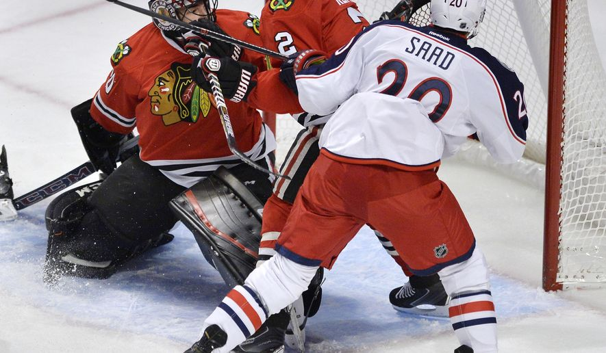 Chicago Blackhawks goalie Corey Crawford (50) makes a save against Columbus Blue Jackets' Brandon Saad (20) while Chicago Blackhawks' Duncan Keith (2), looks on during the first period of an NHL hockey game Saturday, Oct. 17, 2015, in Chicago. (AP Photo/Paul Beaty)