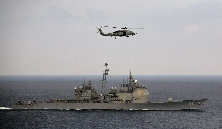 A U.S. Navy helicopter approaches to land on the deck of aircraft carrier USS Theodore Roosevelt (CVN 71), a missile cruiser and a nuclear-powered submarine, as the USS Normady sails in the Bay of Bengal during Exercise Malabar 2015, some 152 miles off eastern coast of Chennai, India, Saturday, Oct. 17, 2015. (AP Photo/Arun Sankar K.) ** FILE **