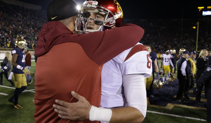 Southern California quarterback Cody Kessler (6) is hugged by interim head coach Clay Helton following an NCAA college football game against Notre Dame, Saturday, Oct. 17, 2015, in South Bend, Ind. Notre Dame won the game 41-31. (AP Photo/Darron Cummings)