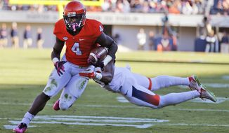 Virginia running back Taquan Mizzell (4) breaks the tackle by Syracuse safety Chauncey Scissum (21) for a touchdown during the first half of an NCAA college football game at Scott Stadium in Charlottesville, Va., Saturday, Oct. 17, 2015. (AP Photo/Steve Helber)