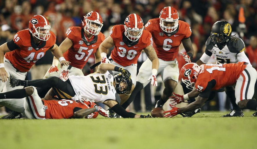 Missouri punt returner Cam Hilton (33) fumbles after being hit by Georgia's Malcolm Mitchell (26) as Malkom Parrish (14) recovers the ball in the second half of an NCAA college football game Saturday, Oct. 17, 2015, in Athens, Ga. Georgia won 9-6. (AP Photo/John Bazemore)