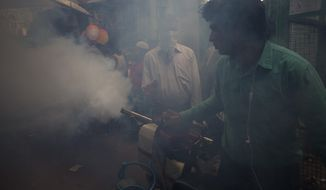 In this Wednesday, Oct. 7, 2015 photo, a municipality worker uses a machine to fog for mosquitoes at a neighborhood in New Delhi, India. At dusk, the foggers come out to spray their sticky-sweet clouds of diesel smoke and insecticide across the Indian capital. Efforts to stop mosquitoes from spreading dengue fever in New Delhi have failed to keep the city from its biggest outbreak in almost two decades: more than 10,190 registered cases, including 32 deaths. (AP Photo/Saurabh Das)