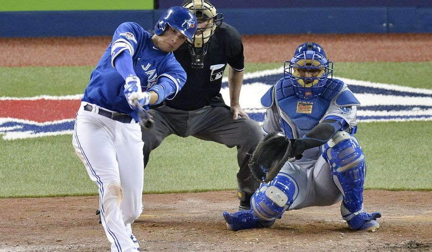 Toronto Blue Jays' Ryan Goins hits a home run off Kansas City Royals' pitcher Kris Medlen as catcher Salvador Perez looks on during the fifth inning in Game 3 of baseball's American League Championship Series on Monday, Oct. 19, 2015, in Toronto. (Chris Young/The Canadian Press via AP) MANDATORY CREDIT
