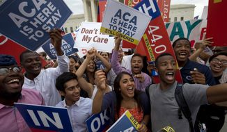 Students cheer outside of the Supreme Court in Washington on June 25, 2015, as they hold up signs supporting the Affordable Care Act (ACA) after the Supreme Court decided that the ACA may provide nationwide tax subsidies. (Associated Press) **FILE**