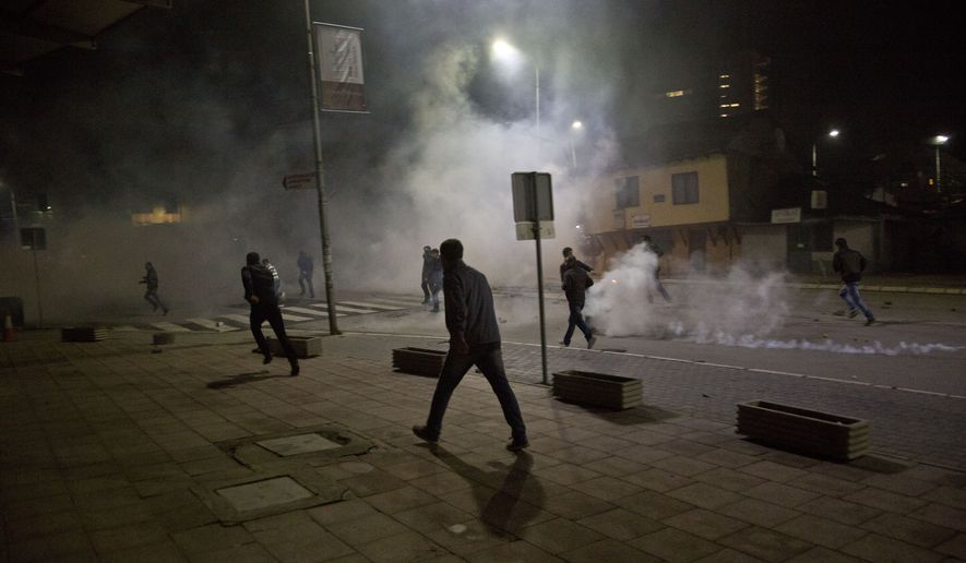 Protester run from tear gas in Kosovo capital Pristina as clashes broke out after the arrest of a prominent opposition politician Albin Kurti on Monday, Oct. 12, 2015. (AP Photo/Visar Kryeziu) ** FILE **