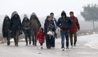 A group of migrants walk on the road near a border line between Serbia and Croatia, near the village of Berkasovo, Serbia, Monday, Oct. 19, 2015. (AP Photo/Darko Vojinovic)