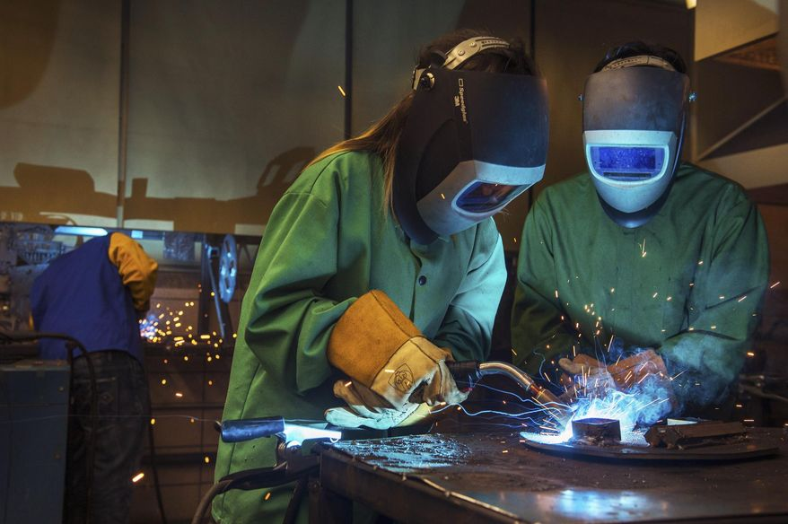 In this Sept. 18, 2015 photo, Manual Academy senior Luis Flores, right, watches as junior Katia Camacho works on gas metal arc welding at the school in Peoria, Ill. Caterpillar, Inc. welders were on hand for a day-long welding camp to offer instruction and advice as the students applied what they learned in class. (David Zalaznik/Journal Star via AP)