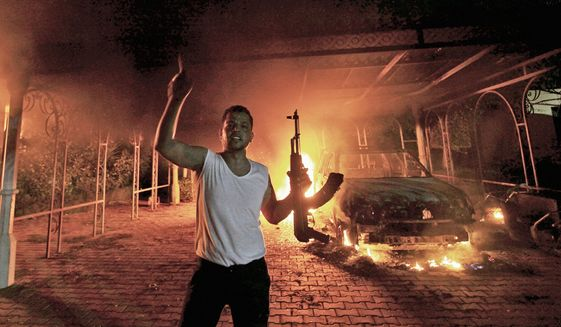 A protester reacts as the U.S. Consulate in Benghazi is seen in flames on September 11, 2012. (Reuters)