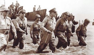 """""""I have returned"""" — Gen. Douglas MacArthur returns to the Philippines with Philippine President Sergio Osmena to his right, Philippine Foreign Affairs Secretary Carlos P. Romulo at his rear, and Lt. Gen. Richard K. Sutherland on his left. Photo taken by Gaetano Faillace. Source: Wikipedia"""