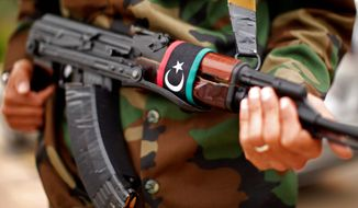 With a Libyan flag on his automatic weapon, a soldier stands guard outside a meeting between Secretary of State Hillary Rodham Clinton and Libya's Transitional National Council President Mustafa Abdel-Jalil at the World Islamic Call Society Headquarters in Tripoli, Libya, on Oct. 18, 2011. (Associated Press) **FILE**