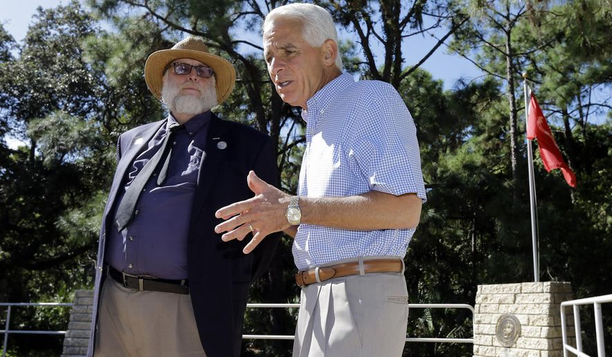 Former Republican Florida Gov. Charlie Crist, right, talks to U.S. Army veteran Jay Alexander at the War Veterans Memorial Park  Tuesday, Oct. 20, 2015, in St. Petersburg, Fla. Crist earlier announced that he was running for Congress as a Democrat. (AP Photo/Chris O'Meara)