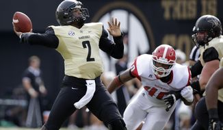 FILE - In this Sept. 19, 2015, file photo, Vanderbilt quarterback Johnny McCrary (2) passes as Austin Peay defensive end Corey Teague (40) rushes in the first half of an NCAA college football game in Nashville, Tenn. Derek Mason keeps sticking with quarterback Johnny McCrary, even though the Vanderbilt sophomore has more interceptions than anyone else in the Southeastern Conference. (AP Photo/Mark Humphrey, File)