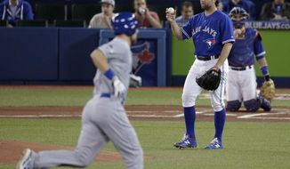 Kansas City Royals' Ben Zobrist rounds the base after a two run home run as Toronto Blue Jays starting pitcher R.A. Dickey looks on during the first inning in Game 4 of baseball's American League Championship Series on Tuesday, Oct. 20, 2015, in Toronto. (AP Photo/Charlie Riedel)