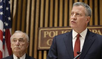 New York City Police Commissioner William Bratton, left, and New York City Mayor Bill de Blasio participate in a media briefing in New York, Wednesday, Oct. 21, 2015. New York Police Department Officer Randolph Holder died Tuesday night after being shot in the head in a gun battle while pursuing a suspect following a report of shots fired, police said. Police on Wednesday named 30-year-old Tyrone Howard as the man they believe killed Officer Holder. (AP Photo/Seth Wenig)