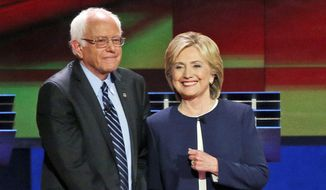 Democratic presidential candidates Sen. Bernie Sanders, I-Vt., left, and Hillary Rodham Clinton talk before the CNN Democratic presidential debate in Las Vegas, in this Oct. 13, 2015, file photo. (AP Photo/John Locher) ** FILE **