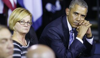 President Obama listens to speakers during an event at the East End Family Resource Center in Charleston, W.Va., Wednesday, Oct. 21, 2015.  Obama was in Charleston to to host a community discussion on the prescription drug abuse and heroin epidemic.  Cary Dixon of Charleston, W.Va. is at left.  (AP Photo/Steve Helber)