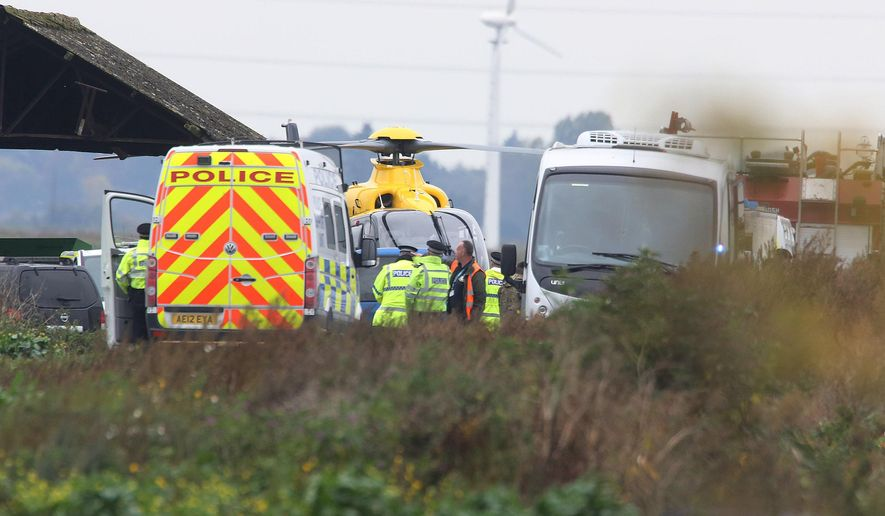 Police seen near the scene of a jet crash, in Redmere, Cambridgeshire, England, Wednesday Oct.  21, 2015. The pilot of a U.S. Marine Corps F-18 was killed Wednesday when the plane crashed near a British air base in eastern England, U.S. and British officials said. (Chris Radburn/PA via AP) UNITED KINGDOM OUT