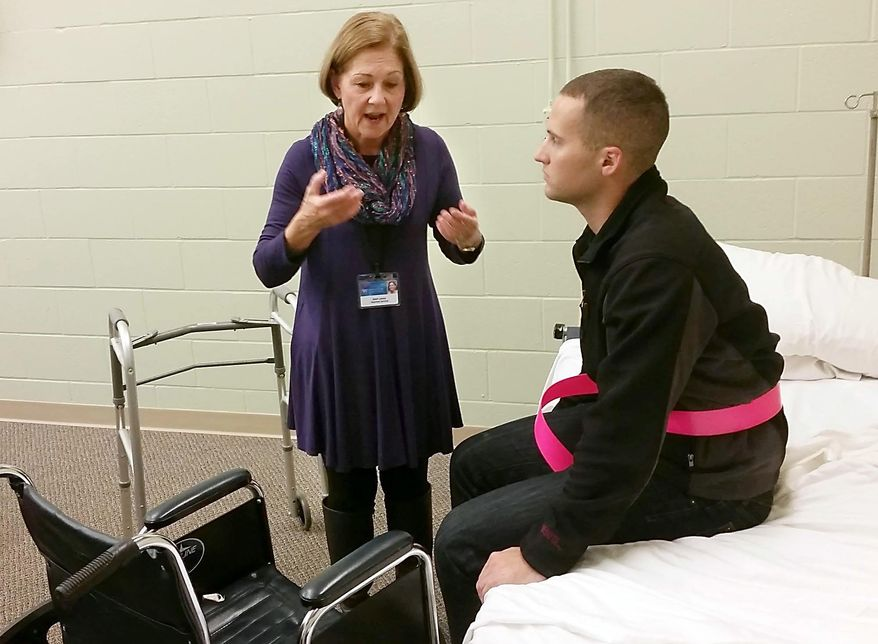 ADVANCE FOR RELEASE MONDAY, OCT. 26, 2015, AT 12:01 A.M. CDT. AND THEREAFTER - In this Oct. 14, 2015 photo, hospice volunteer Joan Lucas, left, explains how to help a patient up from a bed and into a wheelchair in Mankato, Minn. Jon Kearney, attending a training session offered by Mayo Clinic Health System's hospice program, waits to help her demonstrate the technique. (Pat Christman/The Free Press via AP) MANDATORY CREDIT