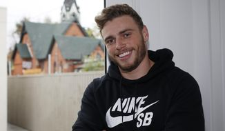 In this Wednesday, Oct. 21, 2015, photo, Gus Kenworthy, a freestyle skier who won a silver medal in Sochi, poses in his home in Denver. The timing, to say nothing of the country, wasn't quite right to tell the world he was gay. And so Kenworthy left Russia last February better known as the compassionate daredevil who adopted several stray dogs he came across in the mountains _ and as the man who was part of an historic U.S. sweep of the first Olympic ski slopestyle contest. (AP Photo/David Zalubowski)