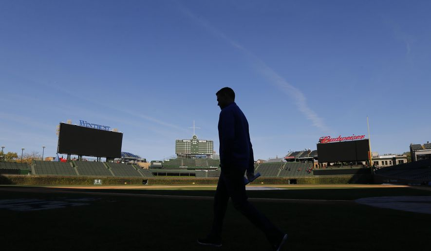 Theo Epstein, President of Baseball Operations for the Chicago Cubs, is silhouetted as he walks across Wrigley Field after talking to reporters the day after his ball club was eliminated in the NLCS by the New York Mets. Thursday, Oct. 22, 2015, in Chicago. (AP Photo/Charles Rex Arbogast)