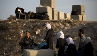 Israeli border police check Palestinian's identification cards at a checkpoint as they exit the Arab neighborhood of Issawiyeh in Jerusalem, Thursday, Oct. 22, 2015. (AP Photo/Oded Balilty)