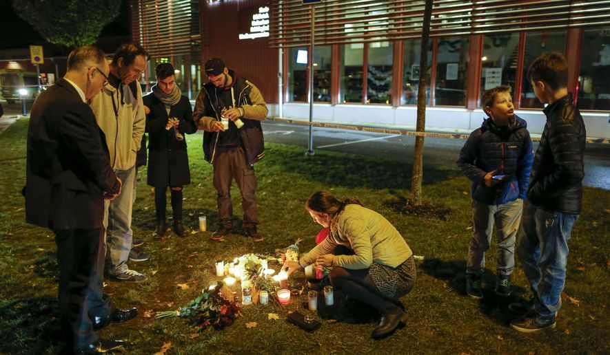 People light candles and lay flower tributes outside the school Thursday afternoon where a masked man stabbed four people Thursday Oct. 22, 2015, in Trollhattan, Sweden. A knife-wielding masked man stabbed four people Thursday at a school in southern Sweden, killing one teacher and a student before being shot by police, authorities said. (Adam Ihse/TT via AP)