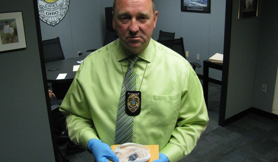 """FILE - In this June 1, 2015, file photo, Bill Collins, police chief in Marion, Ohio, holds """"blue drop"""" heroin laced with the painkiller fentanyl, which officials believe led to more than 30 overdoses and two deaths in the city in late May. At the request of the Ohio Department of Health, researchers from the Centers for Disease Control and Prevention plan to arrive in the state Monday, Oct. 26, 2015, to help find solutions to a wave of deaths attributed to fentanyl-laced heroin. (AP Photo/Mitch Stacy, File)"""
