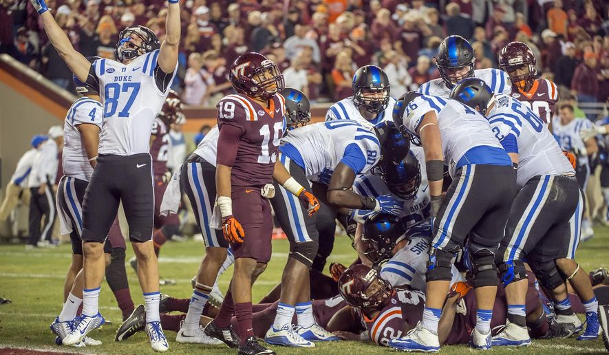 Duke wide receiver Max McCaffrey (87) celebrates after Duke quarterback Thomas Sirk, bottom, crosses the goal and scores an extra point to win after four overtime periods against Virginia Tech during an NCAA college football game, Saturday, Oct. 24, 2015, at Lane Stadium in Blacksburg, Va. Duke defeated Virginia Tech 45-43. (AP Photo/Don Petersen)
