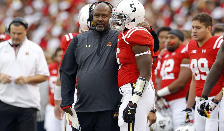 Maryland interim head coach Mike Locksley, left, speaks with running back Wes Brown in the first half of an NCAA college football game against Penn State, Saturday, Oct. 24, 2015, in Baltimore. (AP Photo/Patrick Semansky)