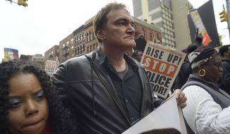 Director Quentin Tarantino, center, participates in a rally to protest against police brutality Saturday, Oct. 24, 2015, in New York. Speakers at the protest said they want to bring justice for those who were killed by police. (AP Photo/Patrick Sison)