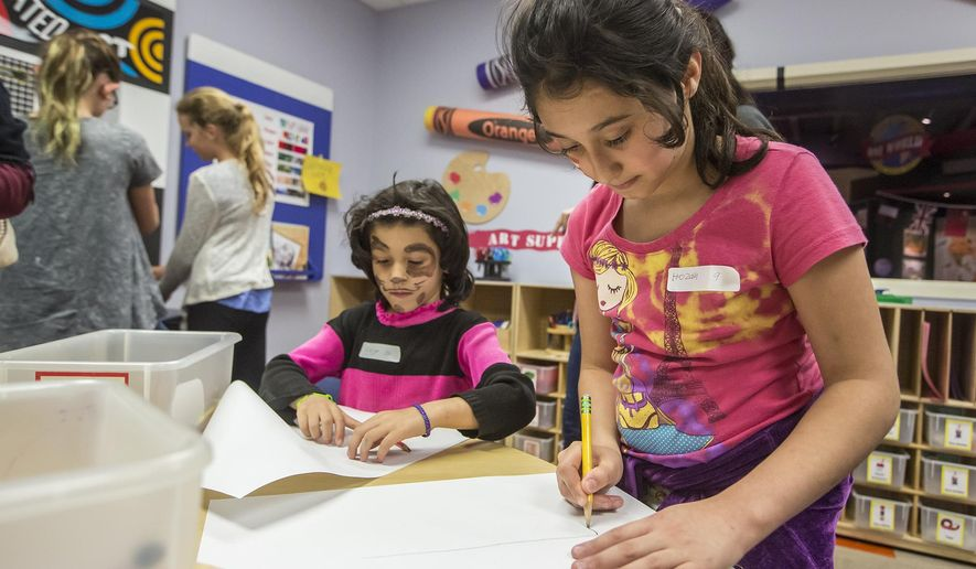 Hozah Al-Hasan, 9, right, draws with her sister, Degn Al-Hasan, 5, during a Rocktown Rallies welcoming party for refugees in the Explore More Discovery Museum in downtown Harrisonburg, Va., on Oct. 16, 2015.   (Daniel Lin/Daily News-Record via AP) MANDATORY CREDIT