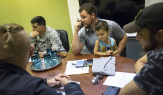 In this Sept. 16, 2015 photo, Donald Hamilton holds his son, Micah, as he meets with employees at his security guard business, in his downtown Colorado Springs, Colo., office. Hamilton tries to hire soldiers with general discharges to give them a second chance. (Christian Murdock/The Gazette via AP) MAGS OUT; MANDATORY CREDIT
