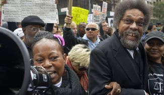 Dr. Cornel West (right) participates in a rally in New York against violence by police on Oct. 24, 2015. Hundreds marched up Sixth Avenue. (Associated Press) **FILE**